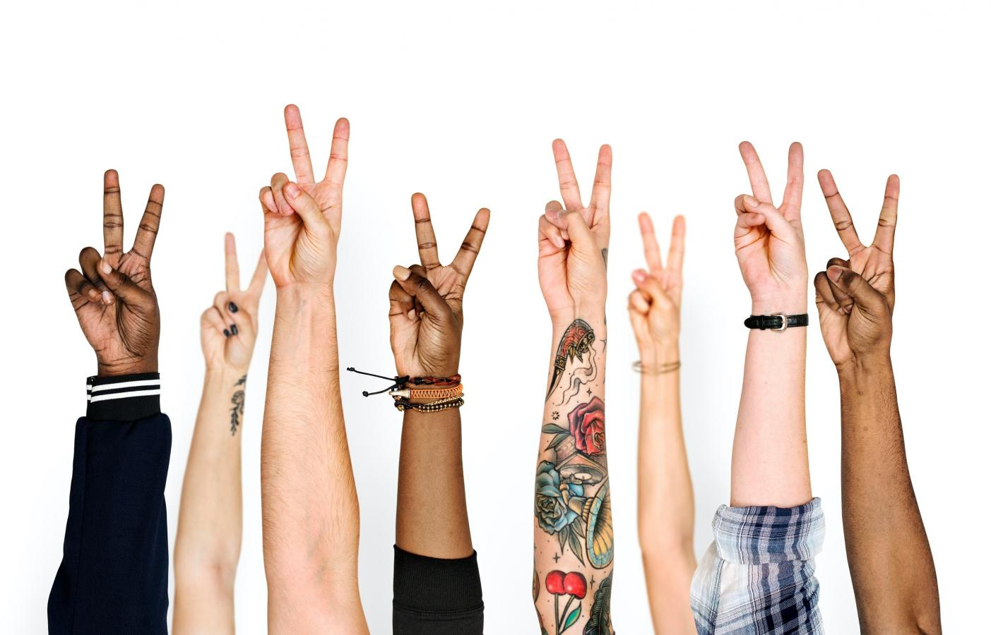 Hands from multiple ethnicities all showing the peace sign